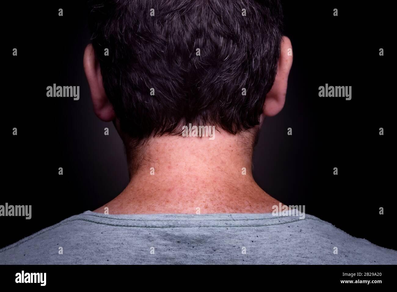 Anonymer kaukasischer Mann mit kurzem braunem Haar und graugrünem Hemd an und freckelt in seinem Nacken von hinten vor dunklem Hintergrund Stockfoto