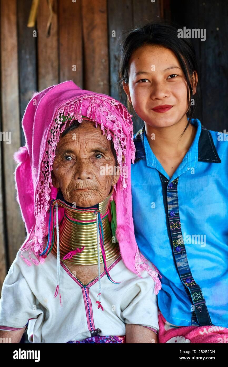 Porträt einer alten Kayan Lahwi-Frau mit Halsspulen aus Messing und traditioneller Kleidung mit ihrer großen Tochter, die die Ringe nicht trägt. Der Lange Stockfoto