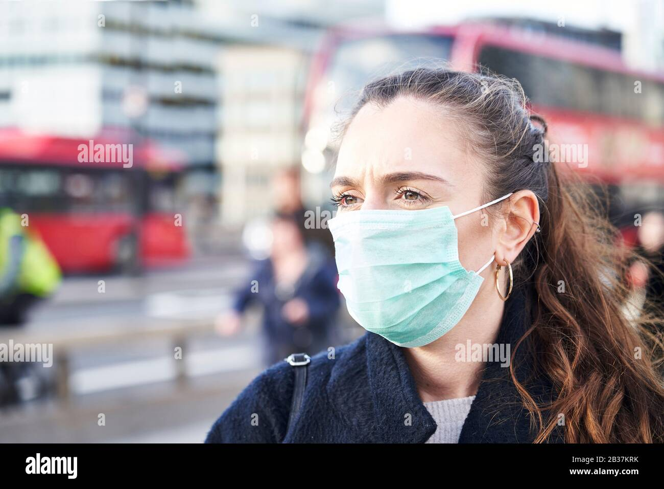 Junge Frau, die Gesichtsmaske trägt, während sie in den Straßen Londons spazieren ging Stockfoto