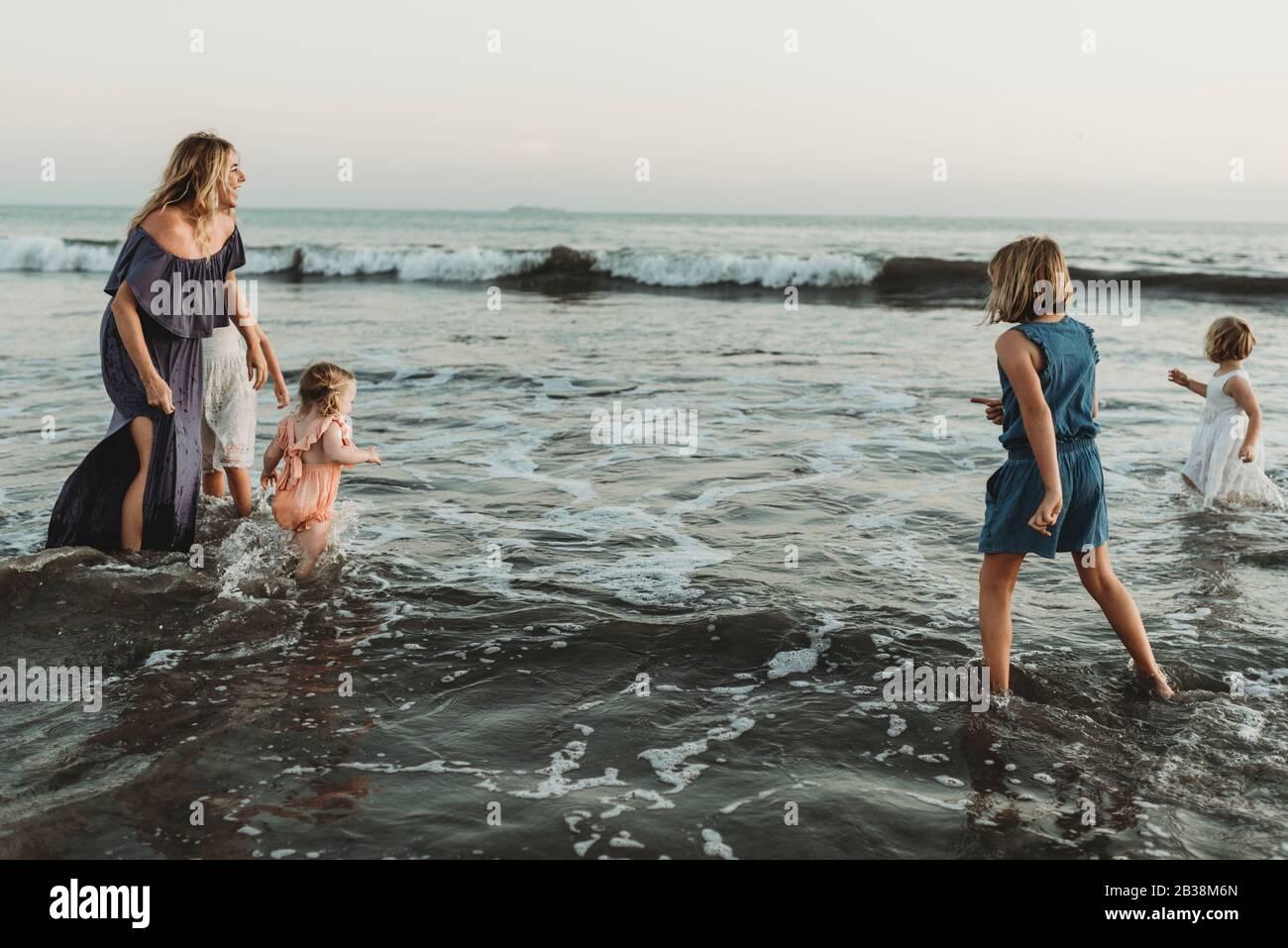 Starke Mutter mit vier Töchtern, die im Ozean bei Sonnenuntergang spielen Stockfoto