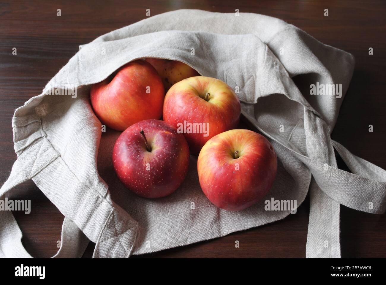 Blick auf die Gruppe der frischen, natürlichen, farbenfrohen gelb-roten Äpfel mit einem neutralen Bettbeutel aus Leinen auf dunklem Sperrholztisch in natürlichem Licht Stockfoto