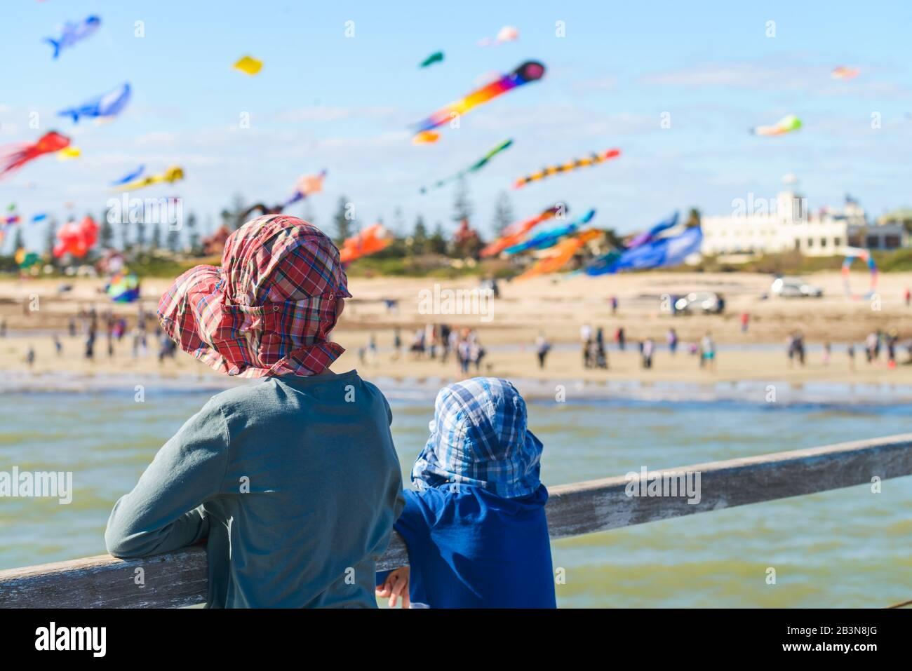 Kinder, die fliegende Drachen aus Semaphore Jetty, South Australia, beobachten Stockfoto