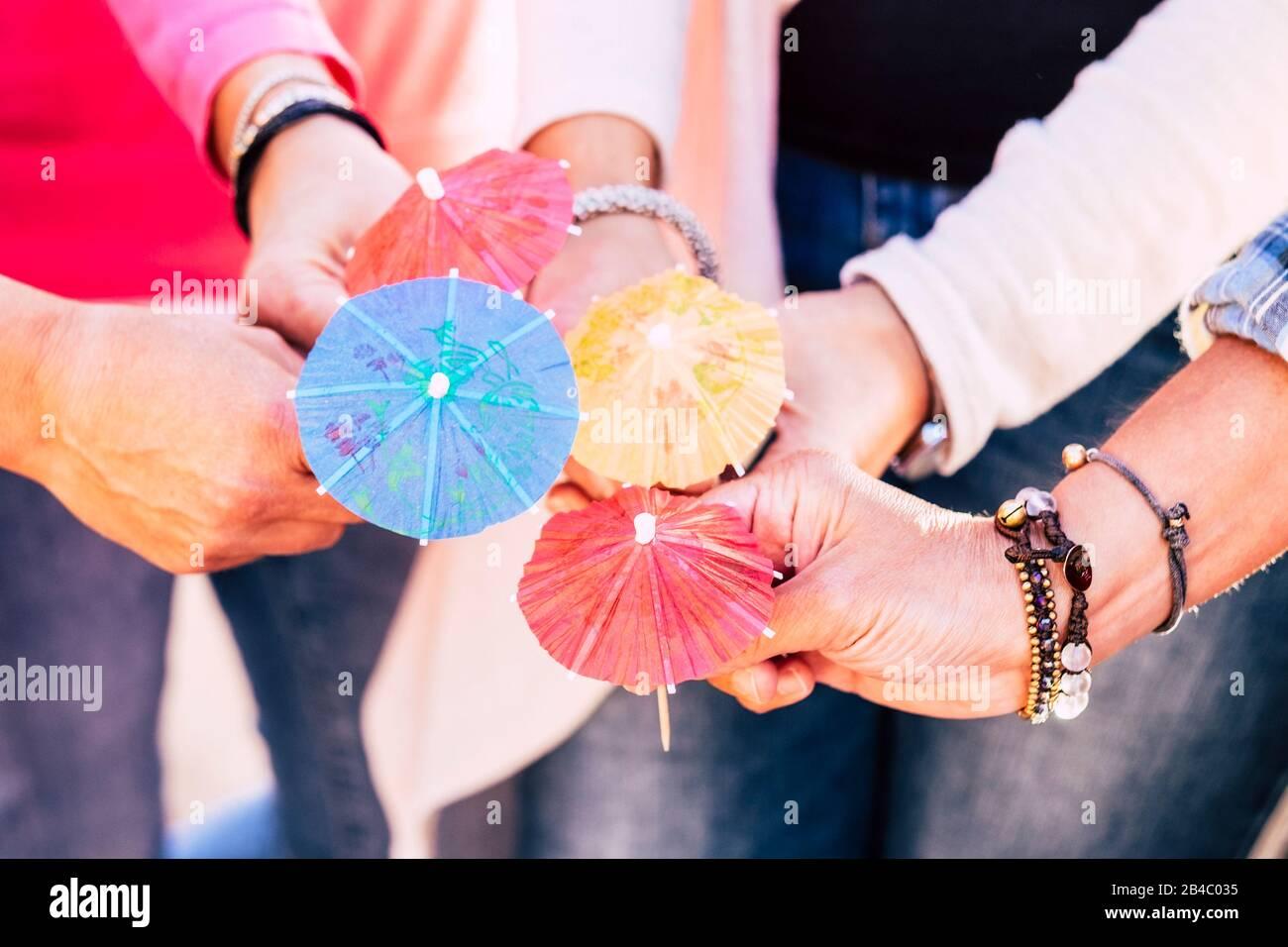 Nahaufnahme mit einer Gruppe von Menschen halten und vier cocktail Schirme zusammen angezeigt - Freundschaft und Zusammenarbeit im Team feiern Konzept Lebensstil Stockfoto