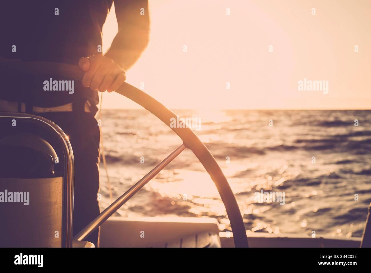 Nahaufnahme der Hand des Menschen auf dem Segelboothelm - Lifestyle-Konzept des Schiffs für schöne Urlaubsdestination - alternatives Menschenleben - Sonnenuntergang und Sonnenlicht im Hintergrund auf dem Ozean Stockfoto