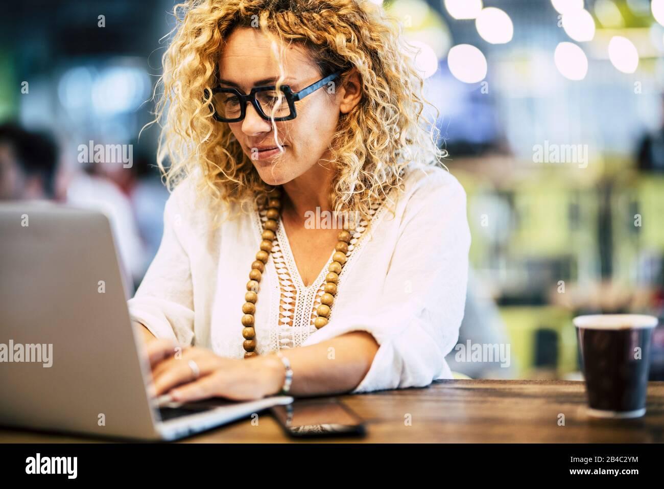 Moderne Erwachsene kaukasische Frau, die an einem Laptop an ihrem Desktop arbeitet - Leute, die mit Technologiekonzept arbeiten - Internetverbindung und entschärfter Hintergrund Stockfoto