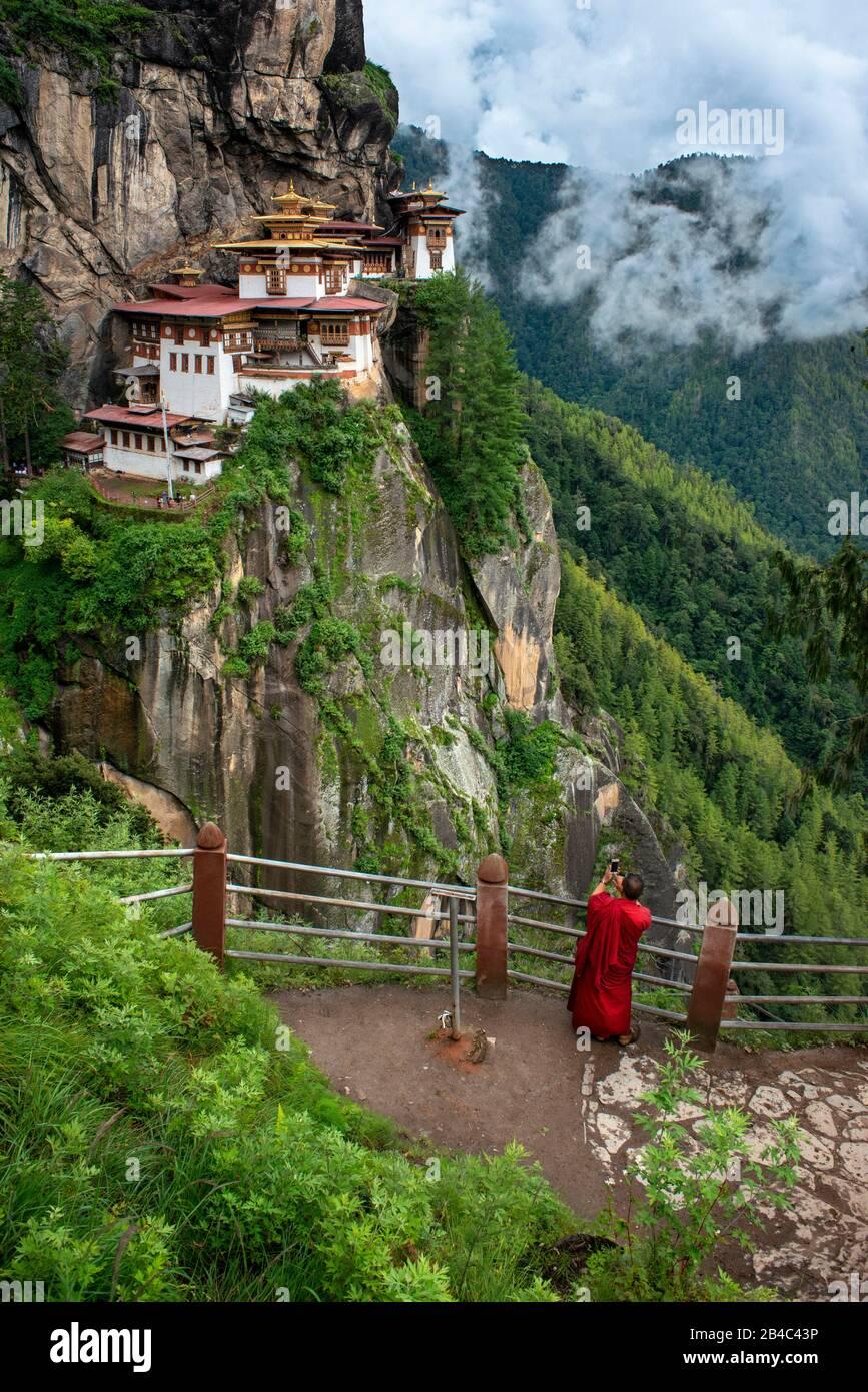 Mönch im Taktsang Goemba oder Tigers nisten Kloster im Paro-Tal, Bhutan, Asien. Das Kloster Paro Taktsang oder Taktsang Palphug und die Tiger-Nest sind es Stockfoto