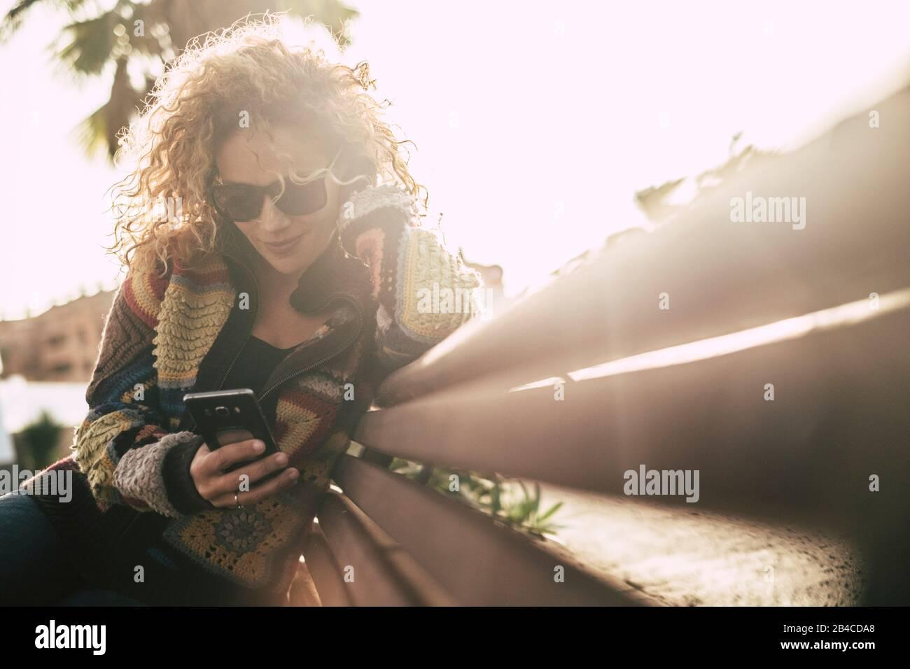 Farben in der Herbstsaison mit schöner, erwachsener, attraktiver blonder lockiger Frau verwenden ein Handy, das auf einem Beanch sitzt und bei Freizeitaktivitäten im Outoor-Bereich aktiv ist - Sonne mit Hintergrundbeleuchtung und hellem Hintergrund Stockfoto