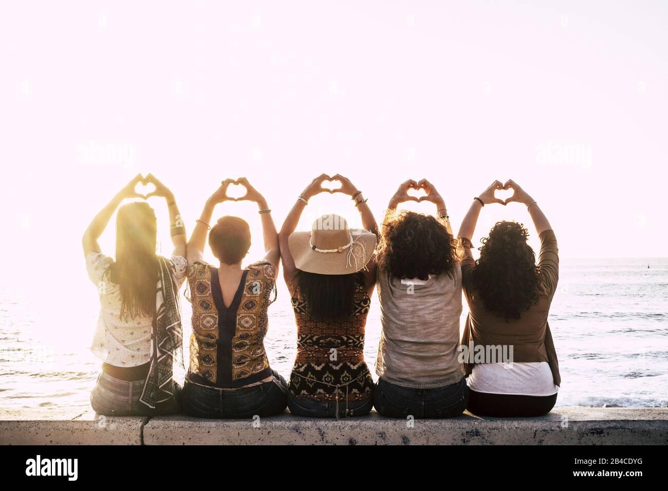 Eine Gruppe glücklicher Menschen im Freien, die Frauen von hinten gesehen haben, die ein Zeichen des Liebeskummer mit den Händen nach oben machen - Beziehungskonzept - Sonnenuntergang und Meer im Hintergrund Stockfoto