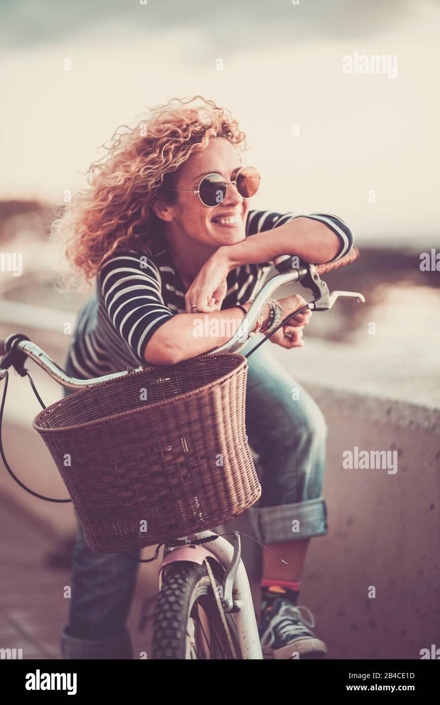 Fröhliche, trendige junge, Erwachsene kaukasische Frau, die auf einem Fahrrad sitzt und lächelt - wunderschönes Frauenporträt - Konzept der Freizeitgestaltung im Freien und des Glücks und des fröhlichen Lebensstils Stockfoto