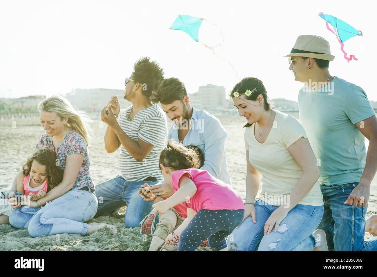 Familien mit Kindern, die bei Sonnenuntergang mit Drachen am Strand fliegen - Erwachsene Freunde, die mit Sohn und Töchtern im Sommerurlaub spielen - Weihnachtskonzept - Stockfoto