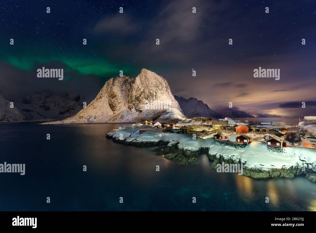 Schöne Nordlichter in Hamnoy, Lofoten Island in Norwegen. Aurora Boreal über dem kleinen Fischerdorf mit seinen traditionellen roten Hütten. Majestätisches g Stockfoto