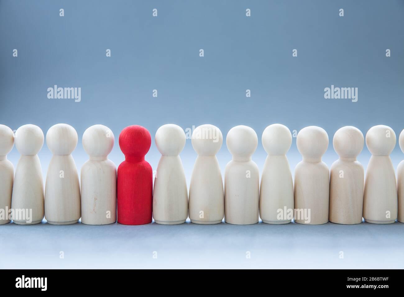 Eine Reihe von menschlichen Figuren mit einem einzelnen, vom Rest abstehenden Menschen, die Individualität repräsentieren und anders sind, wie etwa eine Krankheit Stockfoto