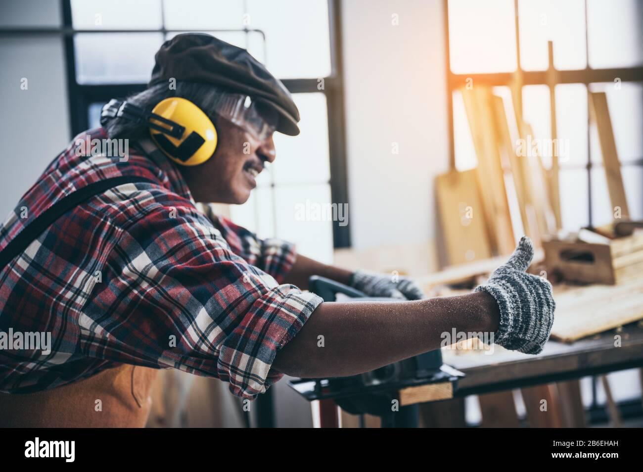 Alter Tischlermeister, der im Tischlerstudio arbeitet Stockfoto