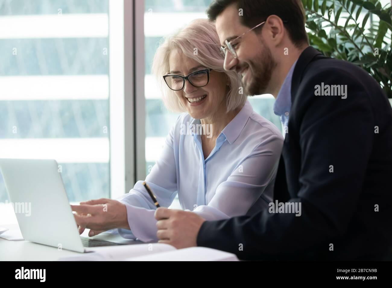 Lachelnde Kollegen Sehen Sich Im Buro Lustige Videos Auf Einem Laptop An Stockfotografie Alamy