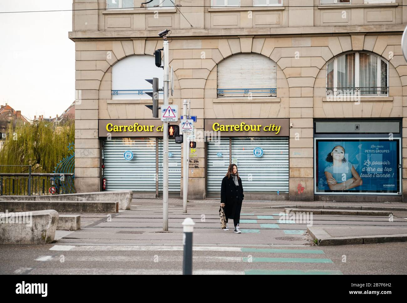 Straßburg, Frankreich - 15. März 2020: Junges Mädchen, das die Straße vor dem Carrefour City Supermarkt durchquert, während Frankreich mit einem Ausbruch des Coronavirus COVID-19 grappt Stockfoto