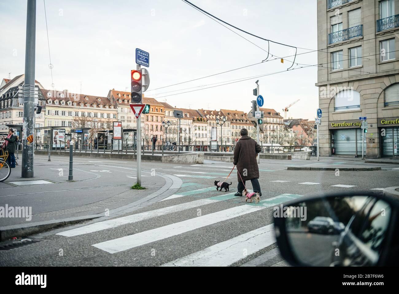 Straßburg, Frankreich - 15. März 2020: Leere Straßen in der französischen Stadt Straßburg mit einer Frau, die Hund spazieren geht, während Frankreich mit einem Ausbruch der Coronavirus-Krankheit COVID-19 grappert Stockfoto