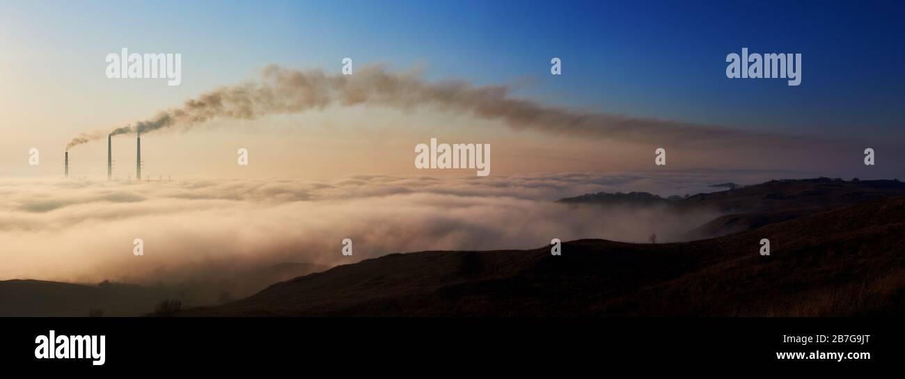 Panoramasicht auf einen Morgenhorizont mit weißen Wolken und drei Röhren, die dunklen Smog in die Atmosphäre ausbringen, Konzept der vom Menschen verursachten Katastrophe, Umweltverschmutzung, Ökologie und Energieerzeugung. Stockfoto