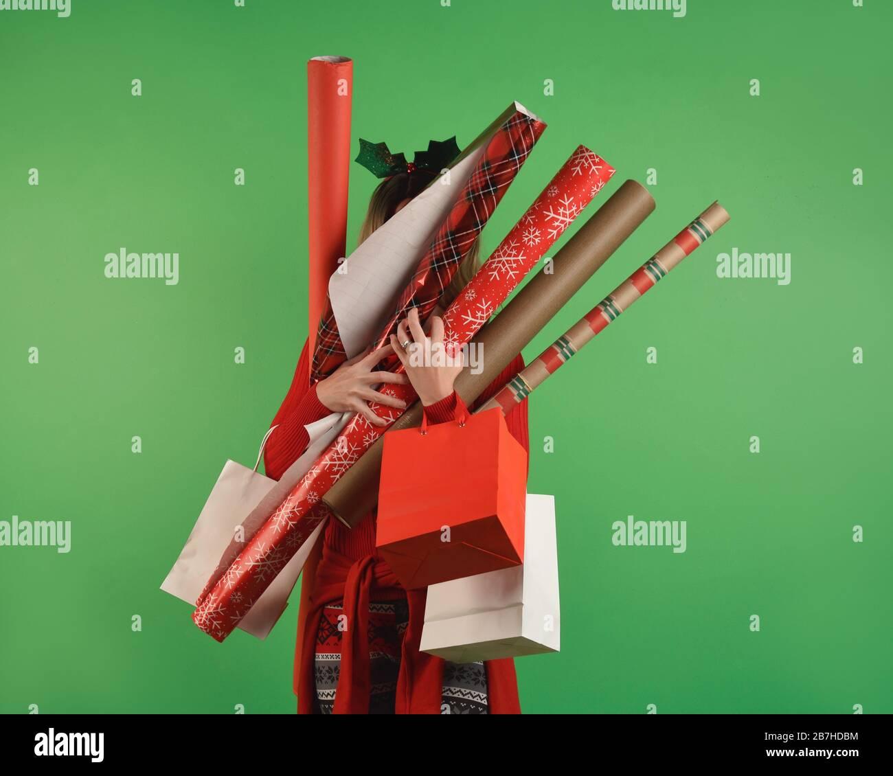 Ein Mädchen hält Weihnachtsverpackungspapier gegen eine solide grüne Wand und ist überwältigt von einer Geschenkidee. Stockfoto