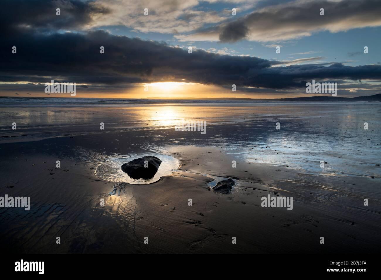 Sonnenuntergang und nasser Sand Stockfoto