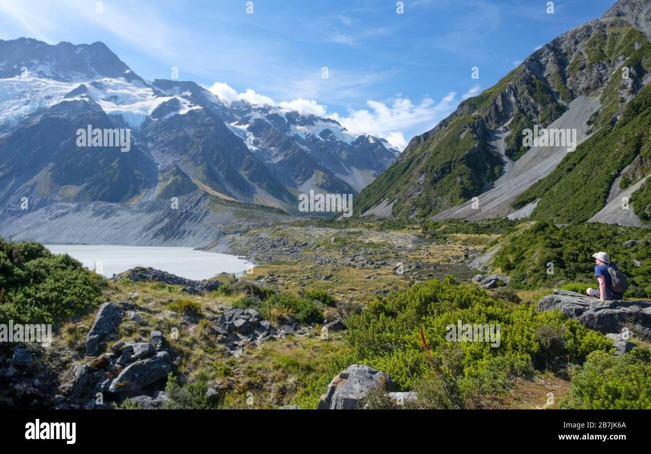 Man on Rock mit Gletschern und schneebedeckten Bergen und See, Aoraki/Mount Cook National Park, South Island, Neuseeland Stockfoto