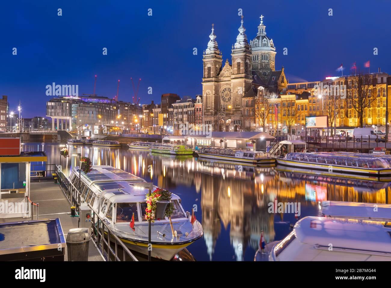 Amsterdam, Niederlande, Kanalszene in der Nacht mit der Basilika Sankt Nikolaus und Flussbooten. Stockfoto