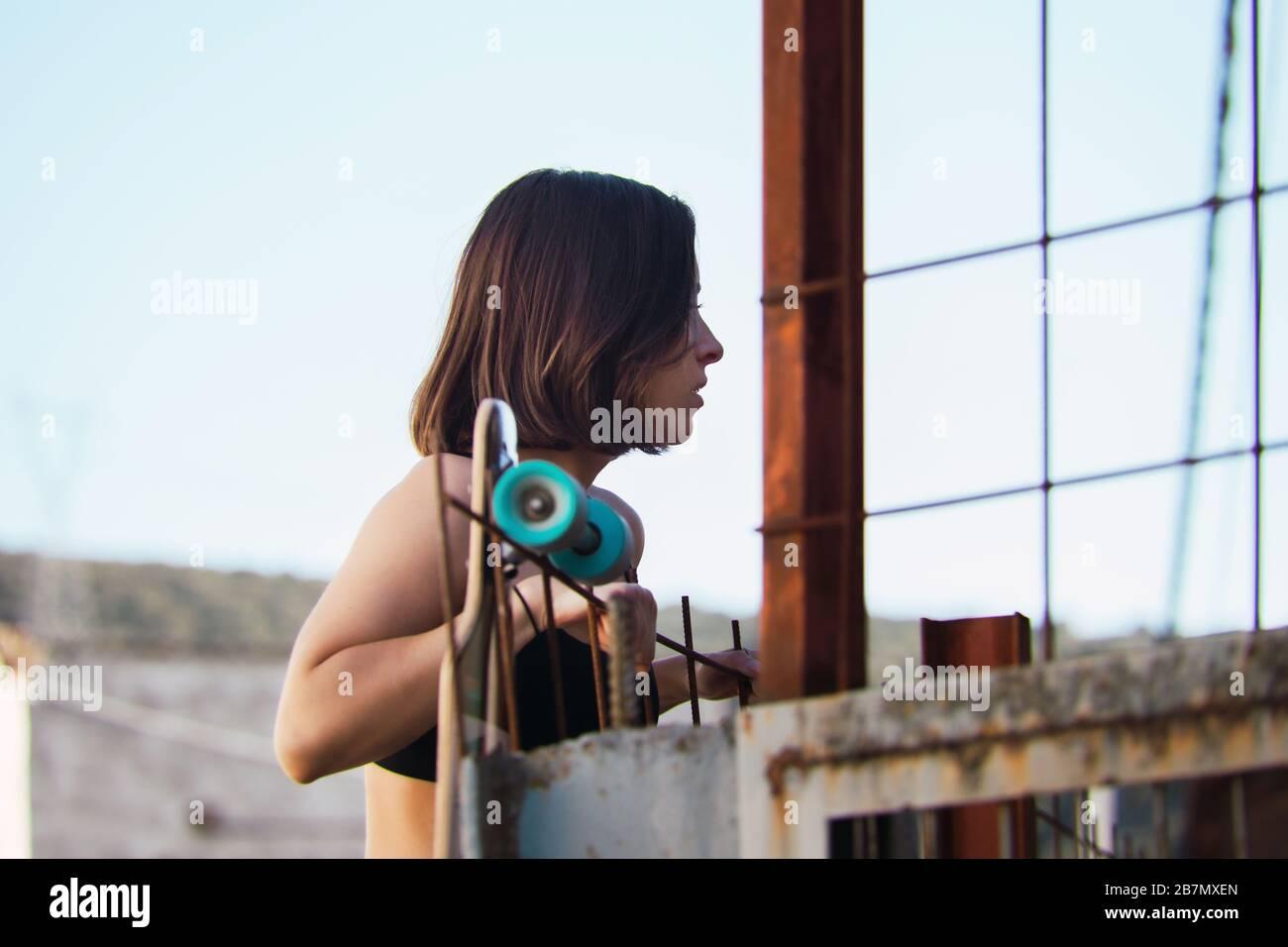 Junge Frau Skater, der versucht, über den Zaun Blick nach innen in einem alten industriellen Straße zu klettern Stockfoto