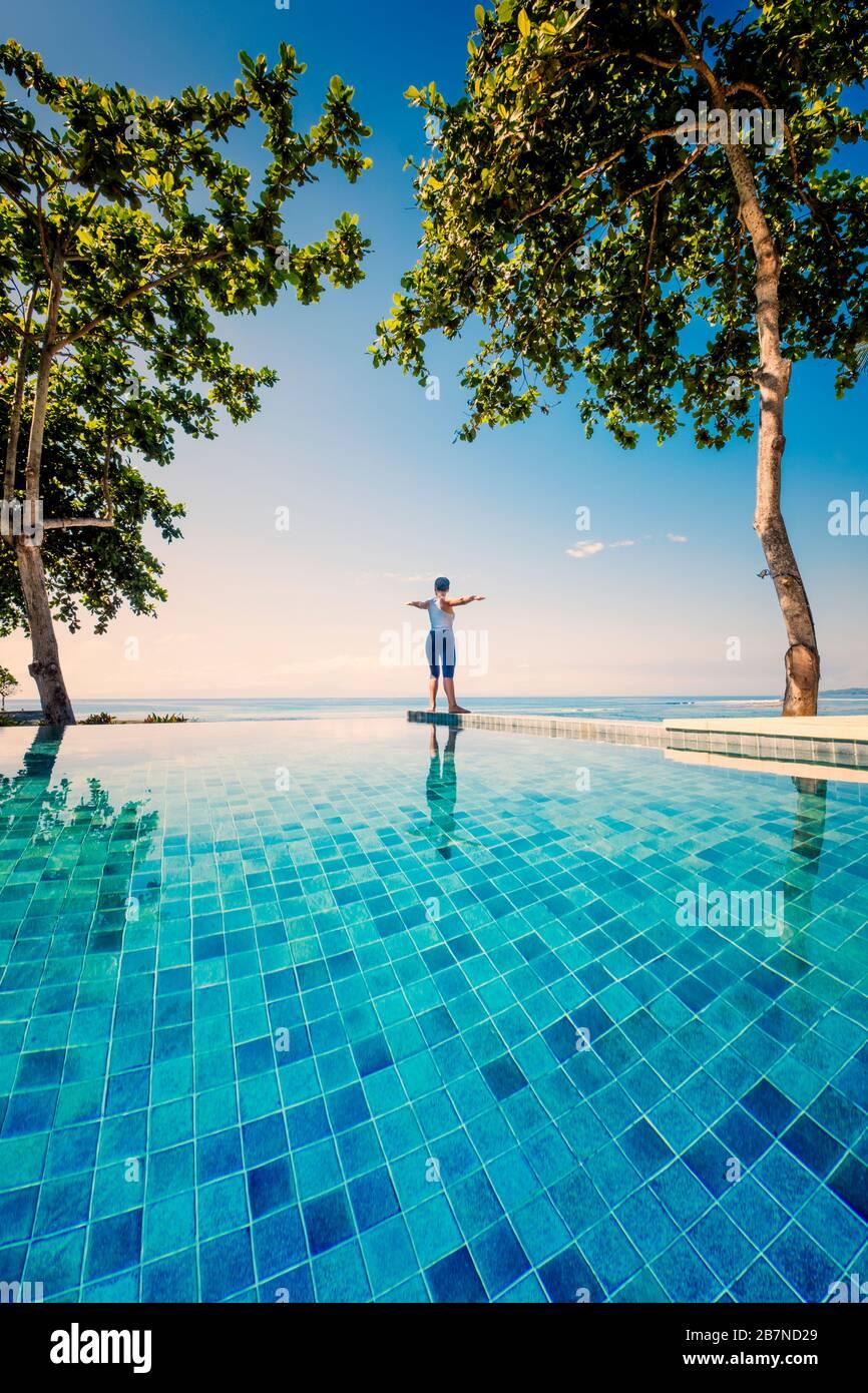 Eine junge Frau, die Yoga unter Palmen neben einem Infinity-Pool praktiziert Stockfoto