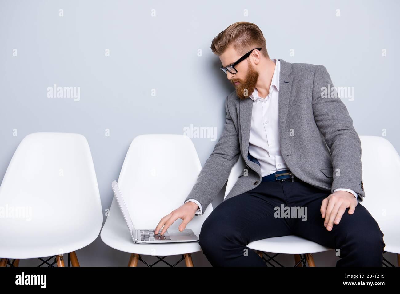 Der seriöse und selbstbewusste Banker des Business man, der auf seinem Laptop tippt, während er in der Halle auf dem Stuhl wartet Stockfoto