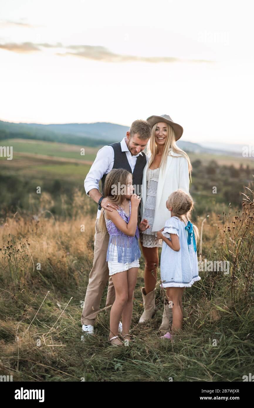 Glücklich lächelnde junge Familie, Vater, Mutter und zwei kleine Töchter, die im Freien Spaß haben und zusammen auf einem wilden Feld stehen. Mutter und Papa sprechen mit Stockfoto
