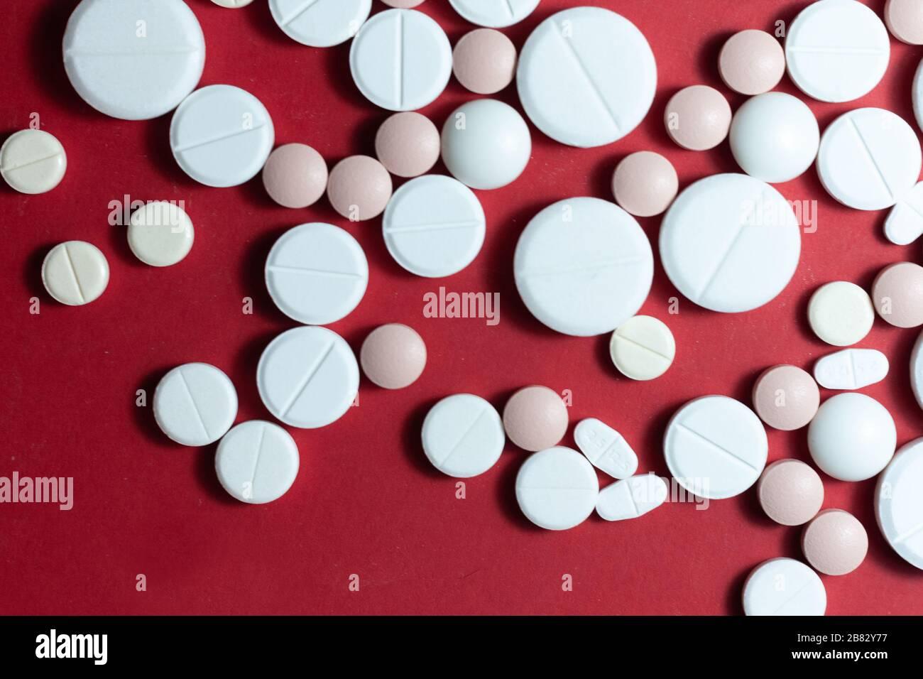 Haufen weißer Pillen, Tabletten, Kapseln auf rotem Hintergrund. Medikamentenverordnung für die Behandlung Medikation Gesundheitskonzept WTH-Kopierraum Stockfoto