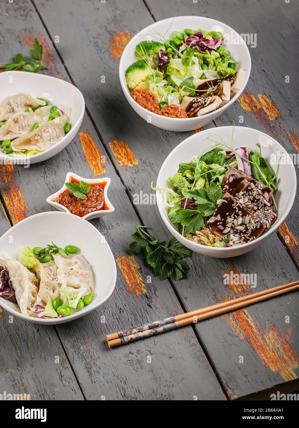 Senkrechtschuss traditionelle Gyozu-Knödel, gekochtes Gemüse mit Reis, Schweinefleisch und würziger Soße. Orientalische Küche Stockfoto