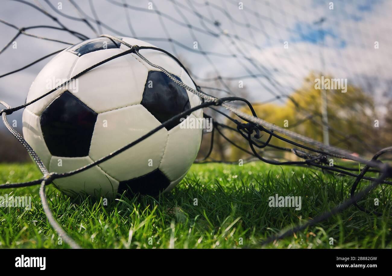 Nahaufnahme eines Fußballballs betritt das Tor und trifft auf das Netz-, Torkonzept. Fußball-Meisterschaftshintergrund, Frühlingsturniere im Freien. Gesunder Sport Stockfoto