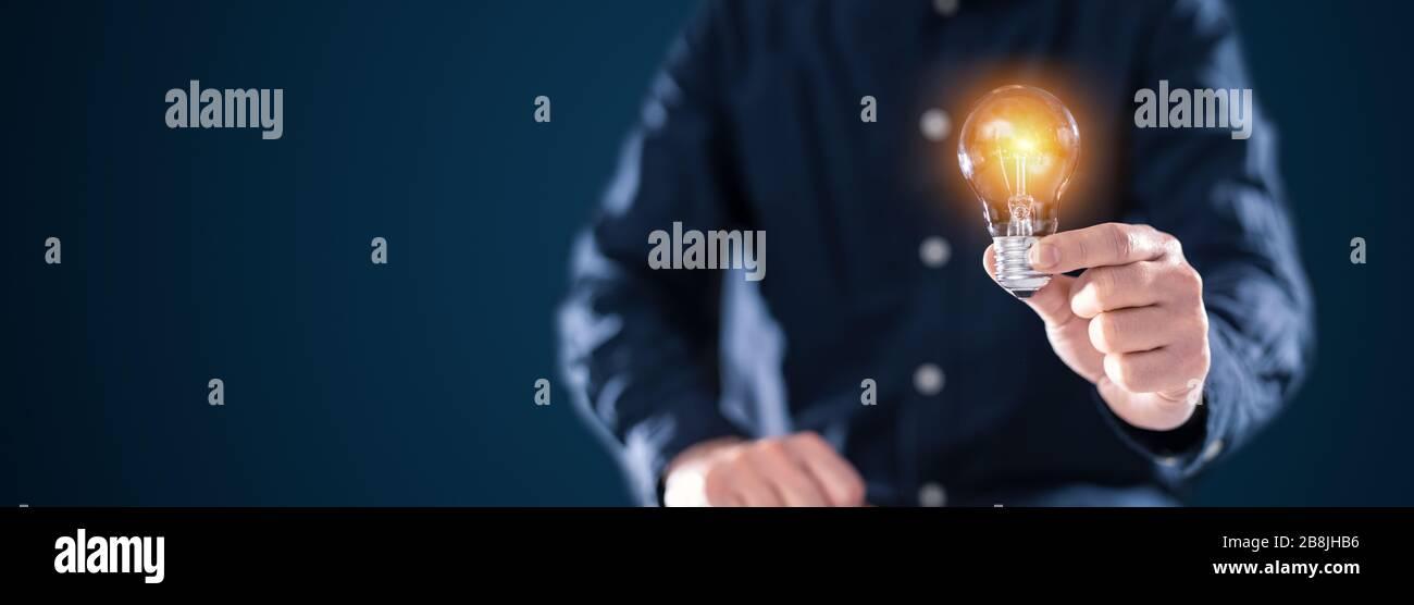 Kreative neue Idee. Innovation, Brainstorming, Inspiration und Lösungskonzepte. Der Mann hält die Glühlampe. Hintergrund des Kopierraums. Stockfoto