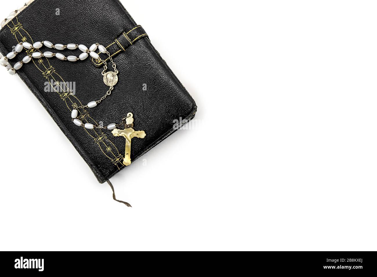 Antiker Gebetbuch, dekoriert mit goldenen Verzierungen und einem Rosenkraut mit weißen Perlen und einem Elfenbeinkreuz Stockfoto