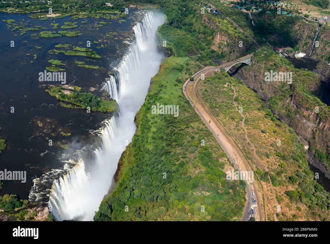 Luftaufnahme der Victoriafälle zwischen Simbabwe und Sambia an einem sonnigen Tag. Wasser, das vom Sambesi River fließt. Von der UNESCO zum Weltkulturerbe ernannt Stockfoto