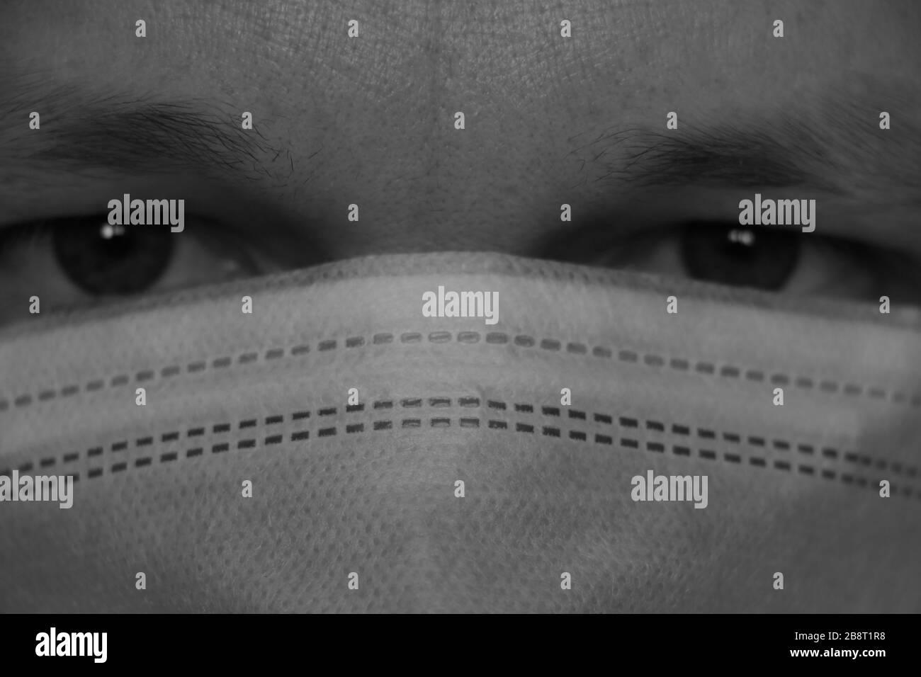 Der Mann hat eine medizinische Schutzmaske, Infektionsschutz, Schutz vor Coronavirus. Starker Blick auf die Kamera, Nahaufnahme. Pandemieepidemie Stockfoto