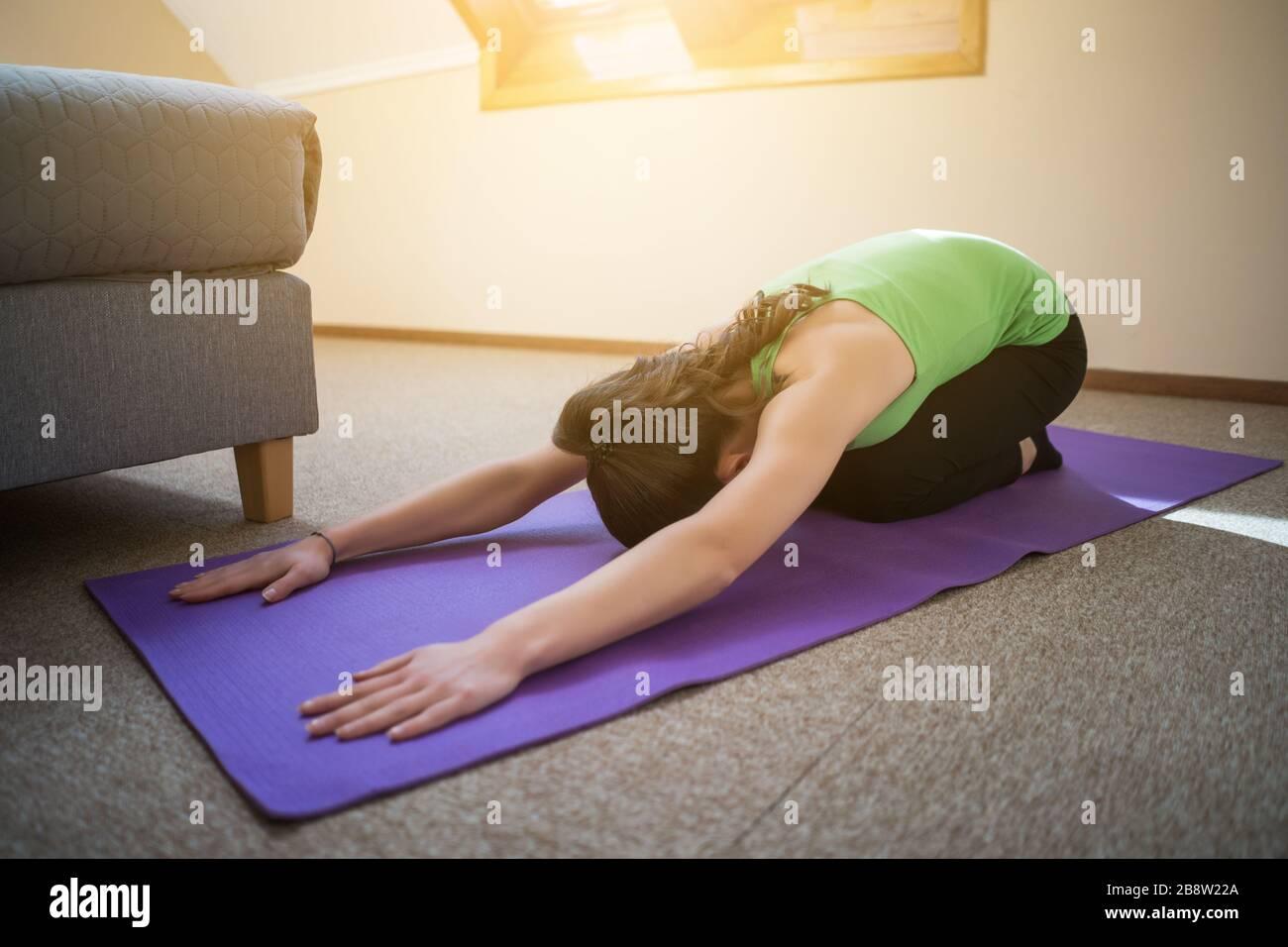 Junge Frau übt zu Hause Yoga aus. Shashankasana/Hare Pose Stockfoto