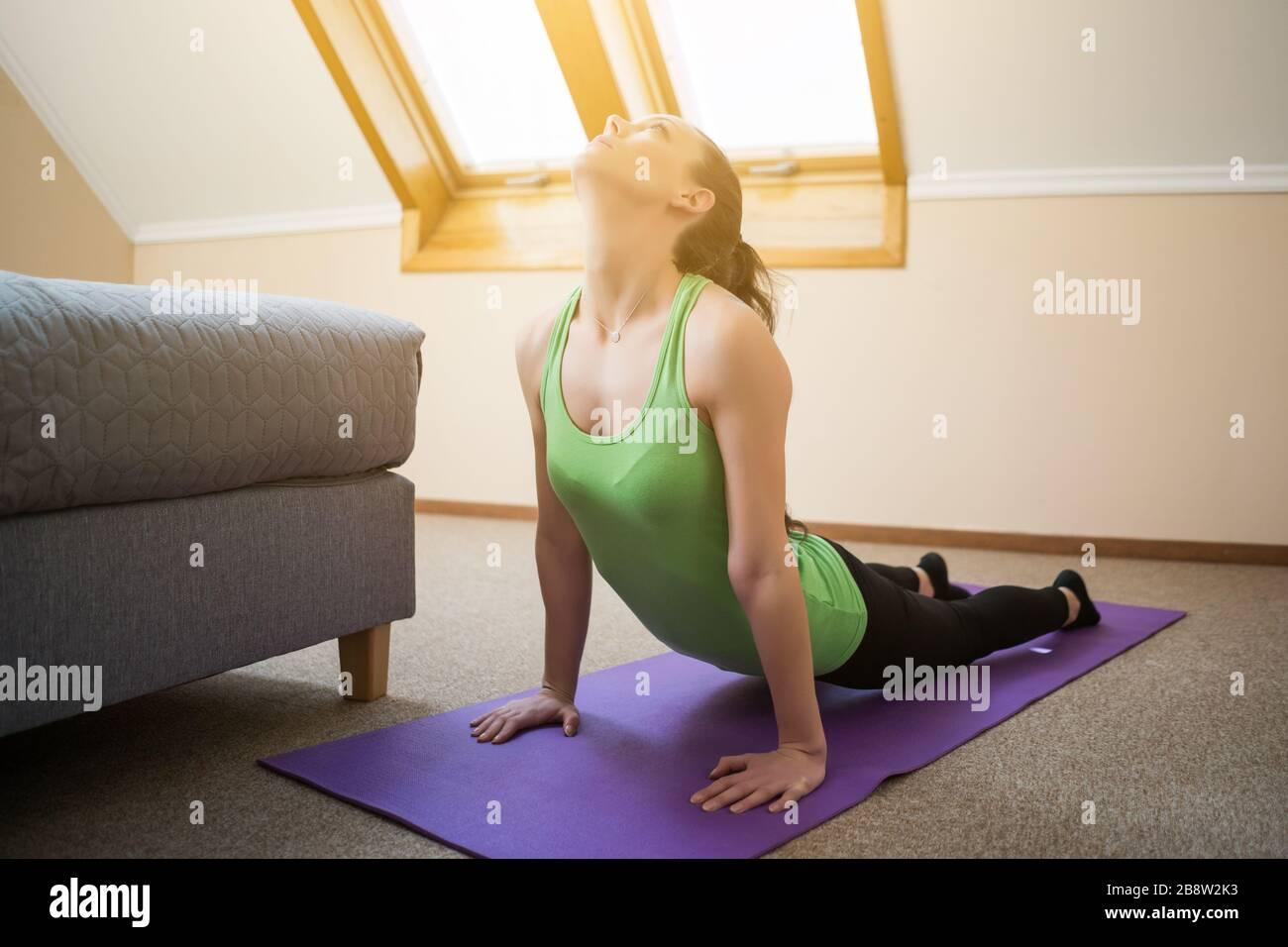 Junge Frau übt zu Hause Yoga aus. Bhujangasana/Cobra Posieren Stockfoto