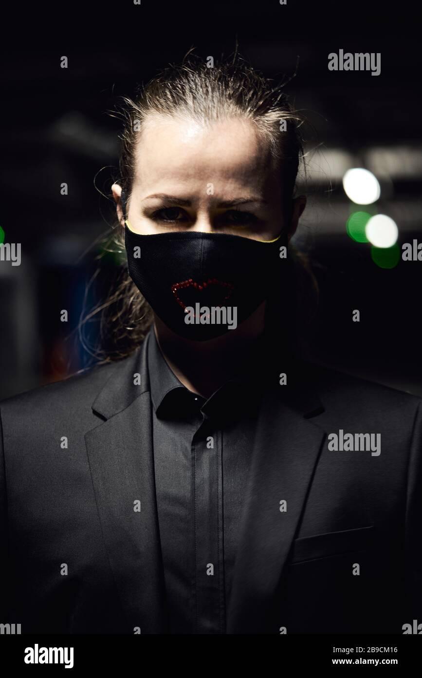Ein junges Mädchen in einer schwarzen Virus-Schutzmaske in einem schwarzen Jackenkanzug auf der Straße. Mode während der viralen Bedrohung Stockfoto
