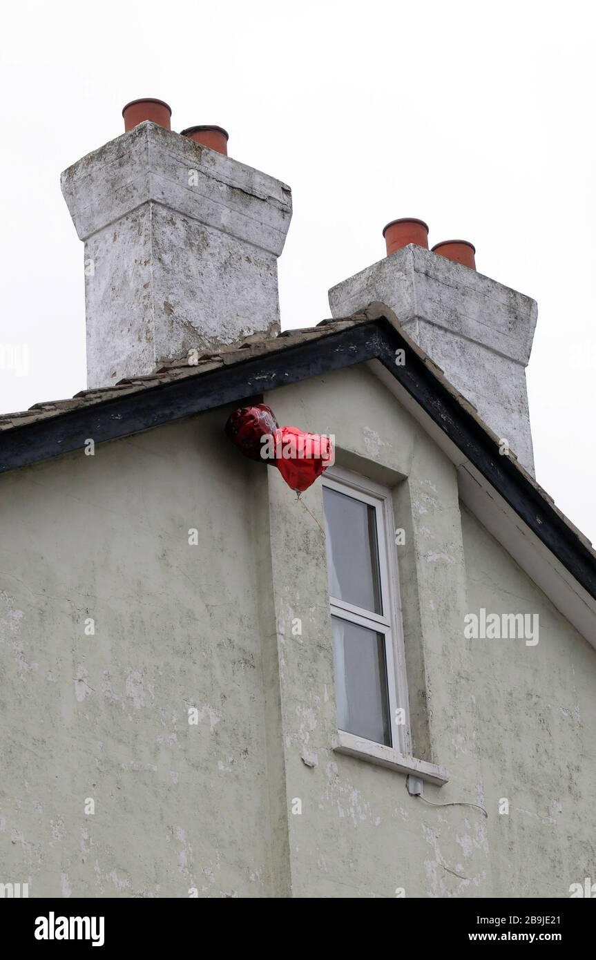 2 Liebe Herz valentine Helium Ballons, die vor einem geschlossenen Fenster in London schweben. Stockfoto