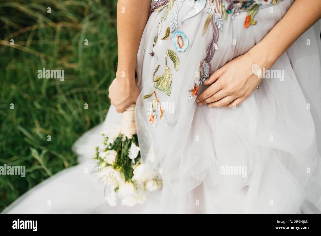 Die Frau in einem schönen Hochzeitskleid mit einem Blumenstrauß in der Hand Stockfoto