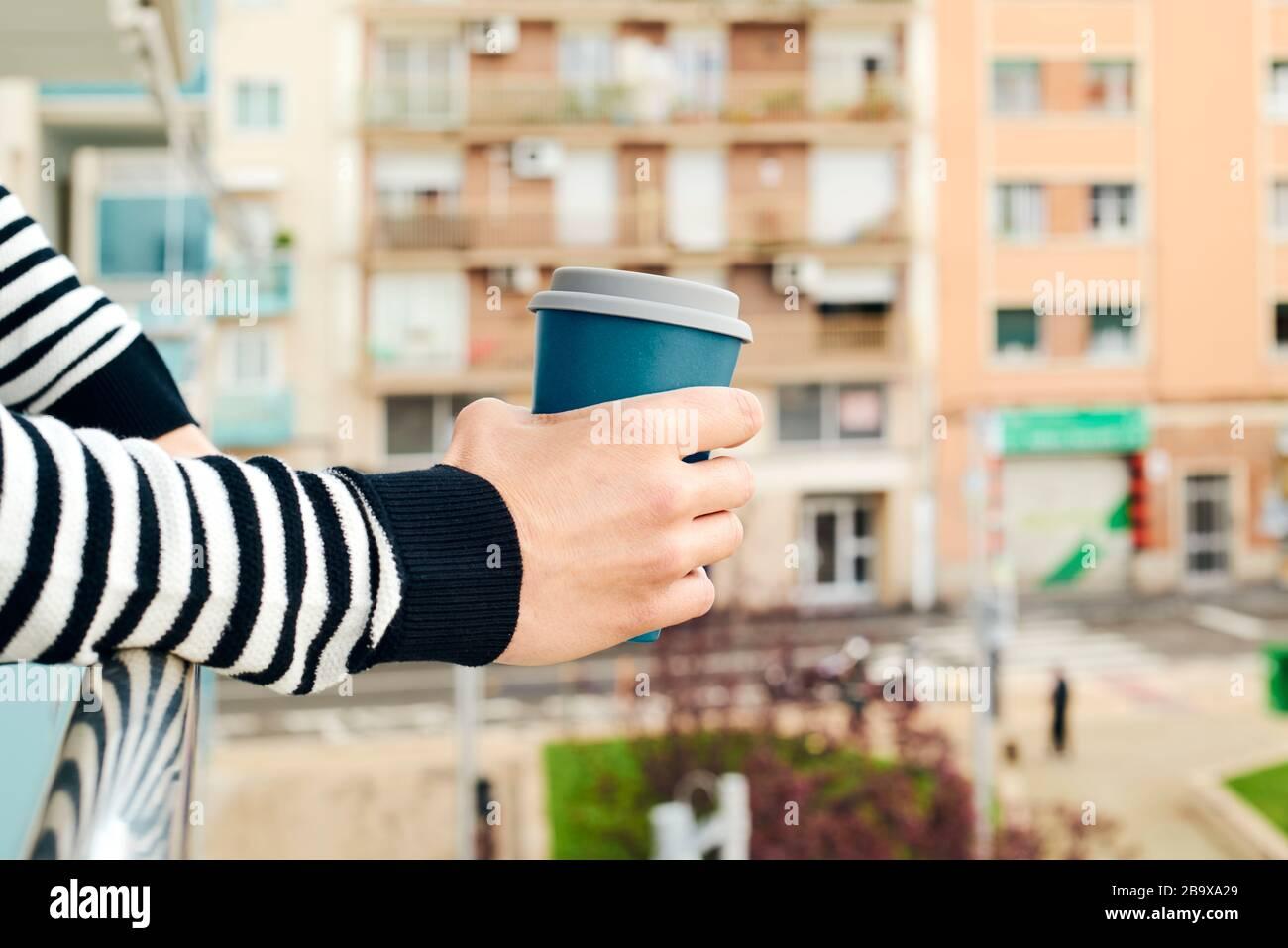 Nahaufnahme eines jungen kaukasischen Mannes mit legeren Kleidungsstücken, Kaffee auf dem Balkon seines Hauses oder eines Hotels Stockfoto