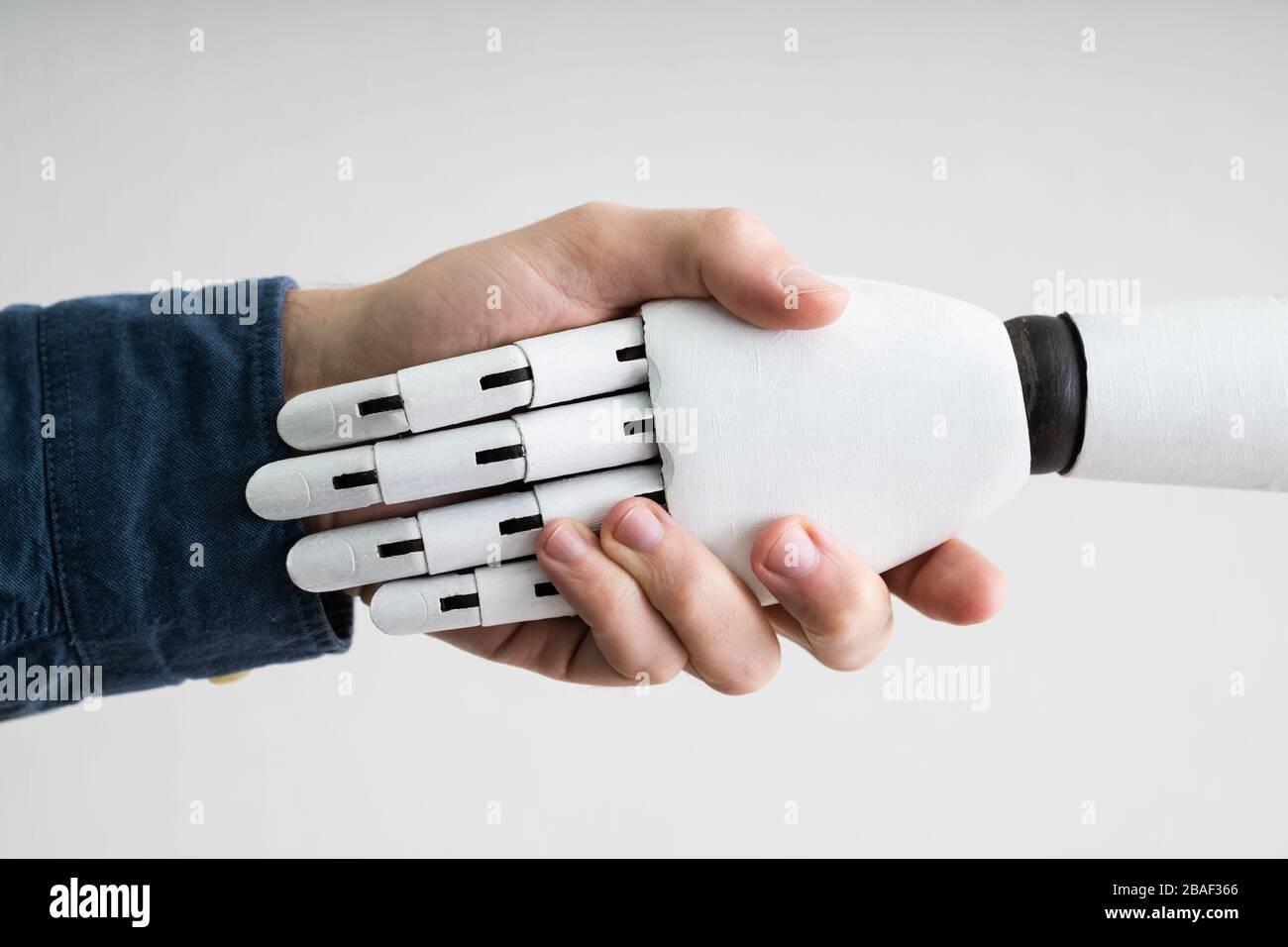 Nahaufnahme der Unternehmer die Hände schütteln mit Roboter Stockfoto