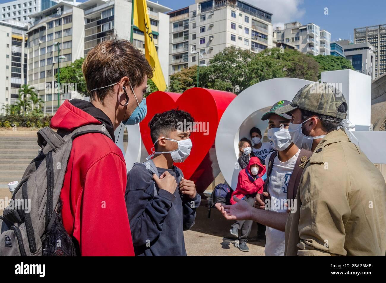 Junge Leute sprechen auf der Plaza Francia in Altamira, bevor sie zu ihrem  Fast-Food-Job gehen. Das Coronavirus traf in Venezuela ein. Das bestätigte  der Co Stockfotografie - Alamy