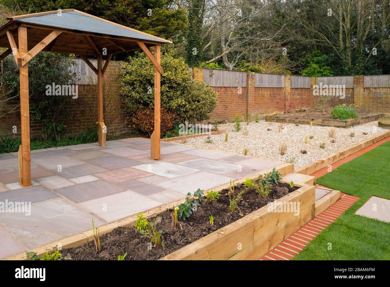 Eine neue, erhöhte Terrasse mit einem Holzgazebo vor einem ...