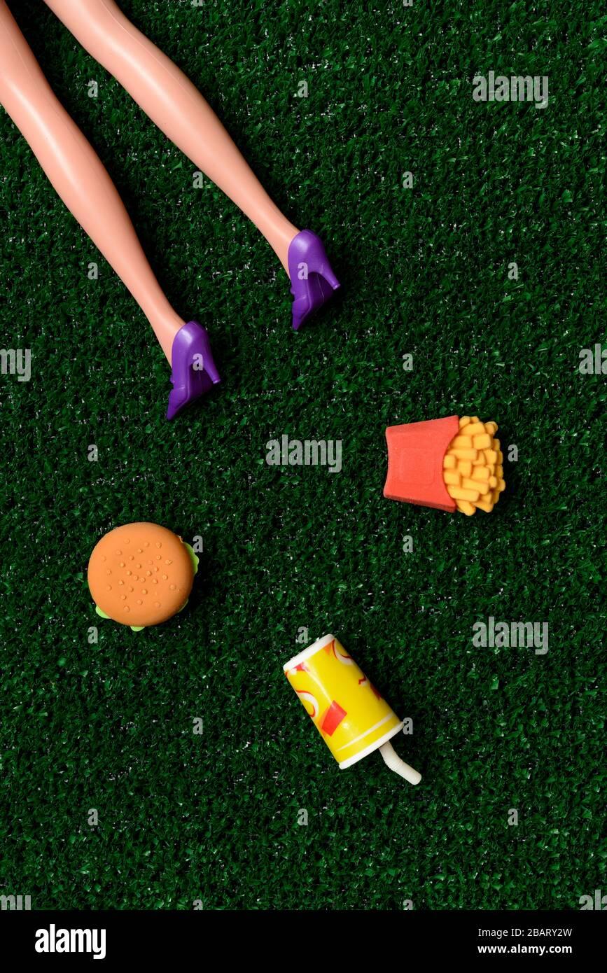 Körper der Frau auf dem Boden in der Nähe von fast Food Stockfoto