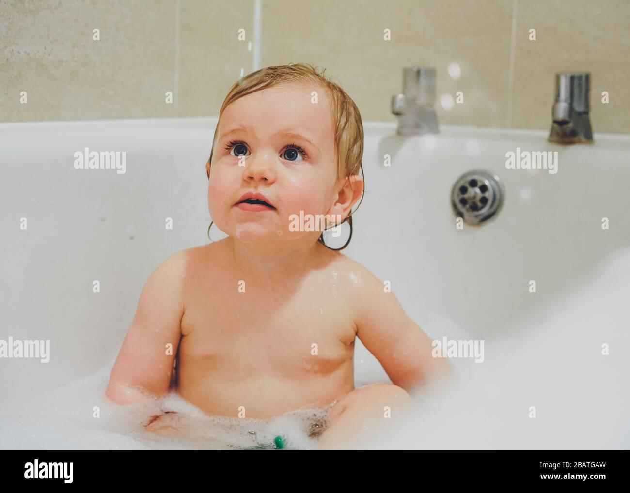 Kleiner Junge, der im Bad mit Blasen spielt Stockfoto