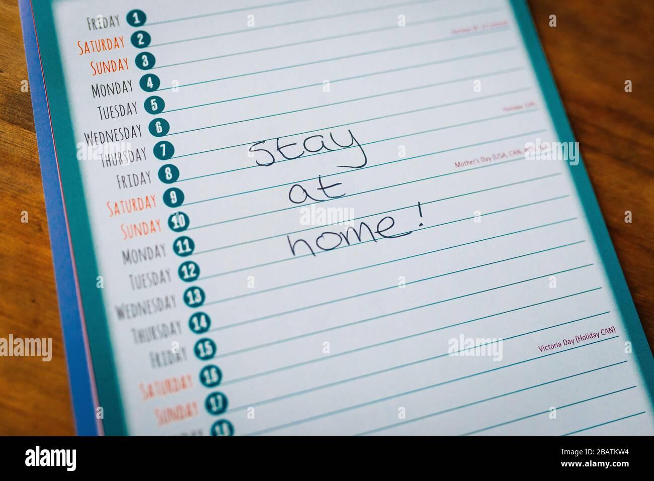 """Coronavirus Kovid19-Sperrquarantäne. Bleiben Sie zu Hause. Kalender, der einen leeren Monat mit den Worten """"zu Hause bleiben"""" handschriftlich anzeigt Stockfoto"""