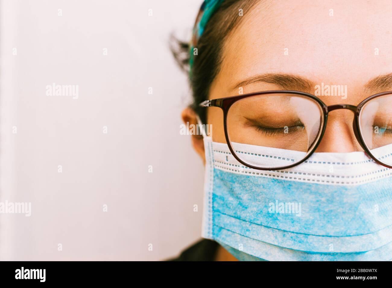 Coronavirus Thema. Asiatische Frau mit Brille, die eine Maske trägt, um sich vor Infizierung zu schützen Stockfoto