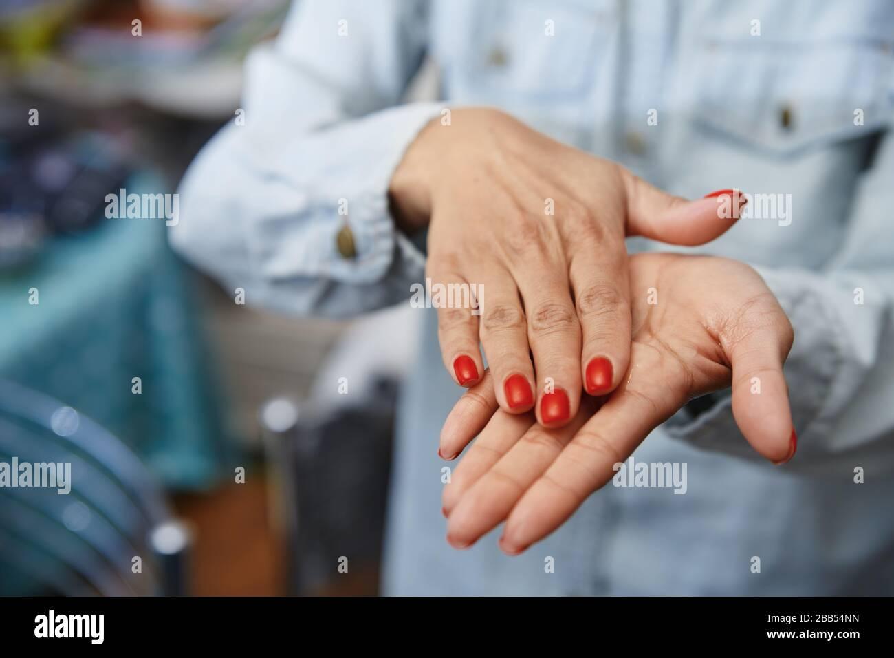 Frau, die zur Desinfektion eine feuchtigkeitsspendende Lotion verwendet Stockfoto